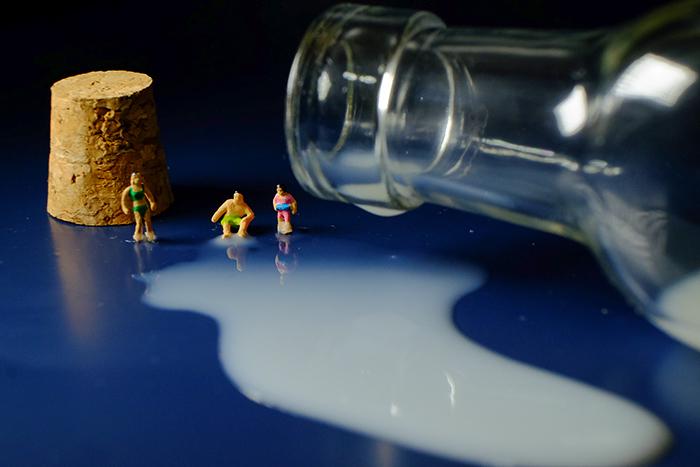 ミニチュア・ヒト写真、ボトルからこぼれるミルクの海にダイブしようとしている人々