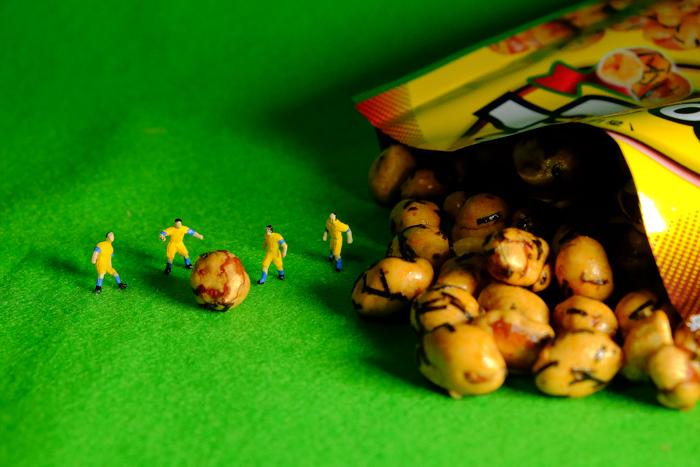 ミニチュア・ヒト写真、次々と繰り出される大きなボールを蹴るサッカー選手達