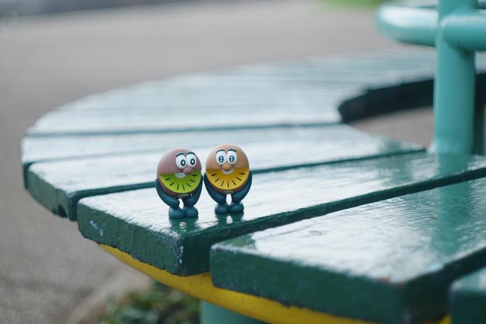 ツバキアキラが撮った、ゼスプリキウイブラザーズのフィギュア。丸くカーブを描いたベンチの上で、遠心力に引っ張られているキウイブラザーズ。